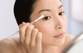 Asian woman applying eye shadow
